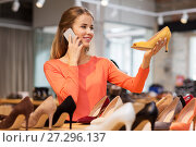 young woman calling on smartphone at shoe store. Стоковое фото, фотограф Syda Productions / Фотобанк Лори