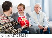 Купить «Son gives gift to parents», фото № 27296881, снято 19 марта 2019 г. (c) Яков Филимонов / Фотобанк Лори