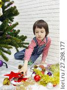 Купить «Little boy in red plaid shirt and denim overalls decorates a Christmas tree», фото № 27298177, снято 16 декабря 2017 г. (c) ivolodina / Фотобанк Лори