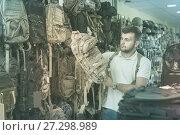 Купить «Man choosing textile backpack gun in military shop», фото № 27298989, снято 4 июля 2017 г. (c) Яков Филимонов / Фотобанк Лори