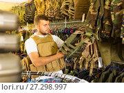 Купить «Male customer choose bulletproof vest», фото № 27298997, снято 4 июля 2017 г. (c) Яков Филимонов / Фотобанк Лори