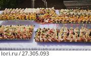 Купить «Cooked festive treats for guests on the occasion of the wedding. Beautifully decorated buffet. Nature. Celebration.», видеоролик № 27305093, снято 29 октября 2017 г. (c) Mikhail Davidovich / Фотобанк Лори