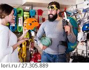 Купить «Climbers examining alpinism equipment items in sports shop», фото № 27305889, снято 24 февраля 2017 г. (c) Яков Филимонов / Фотобанк Лори