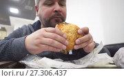 Hungry man eating big hamburger in fast food cafe. Стоковое видео, видеограф Курганов Александр / Фотобанк Лори