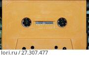 Купить «vintage orange audio cassette tape with a blank label», видеоролик № 27307477, снято 24 января 2017 г. (c) Курганов Александр / Фотобанк Лори