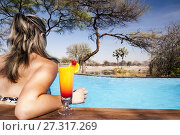 Young woman with drink in swimming pool at Onguma Tented Camp, Onguma Game Reserve, Namibia, Africa. (2017 год). Редакционное фото, фотограф Bill Gozansky / age Fotostock / Фотобанк Лори