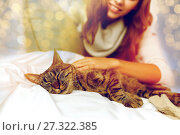 Купить «happy young woman with cat lying in bed at home», фото № 27322385, снято 15 октября 2016 г. (c) Syda Productions / Фотобанк Лори