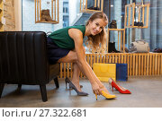 Купить «young woman trying high heeled shoes at store», фото № 27322681, снято 22 сентября 2017 г. (c) Syda Productions / Фотобанк Лори