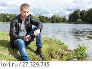 Купить «Мужчина сидит на берегу озера и читает сообщение на телефоне», фото № 27329745, снято 17 сентября 2011 г. (c) Кекяляйнен Андрей / Фотобанк Лори