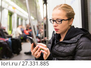 Купить «Young girl reading from mobile phone screen in metro.», фото № 27331885, снято 18 февраля 2019 г. (c) Matej Kastelic / Фотобанк Лори