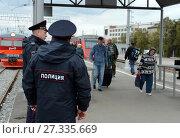 Полицейские контролируют общественный порядок на железнодорожной платформе у пригородных электропоездов (2015 год). Редакционное фото, фотограф Free Wind / Фотобанк Лори