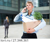 Купить «Young businessman with box is talking phone and searching new job», фото № 27344361, снято 15 июля 2017 г. (c) Яков Филимонов / Фотобанк Лори