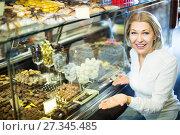 Купить «Woman selecting chocolates and confectionery», фото № 27345485, снято 31 марта 2020 г. (c) Яков Филимонов / Фотобанк Лори