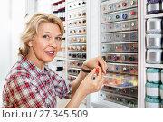 Купить «Mature glad woman customer picking various buttons», фото № 27345509, снято 23 мая 2019 г. (c) Яков Филимонов / Фотобанк Лори