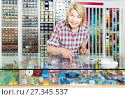 Купить «portrait of female cashier standing at cash desk in embroidery shop», фото № 27345537, снято 15 декабря 2018 г. (c) Яков Филимонов / Фотобанк Лори
