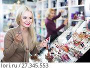 Купить «Young woman choosing lip plumper», фото № 27345553, снято 24 января 2018 г. (c) Яков Филимонов / Фотобанк Лори