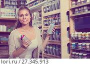Купить «woman choosing paint in aerosol can in shop», фото № 27345913, снято 21 октября 2018 г. (c) Яков Филимонов / Фотобанк Лори