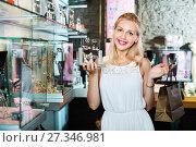Купить «Portrait of young cheerful woman choosing earrings», фото № 27346981, снято 26 марта 2019 г. (c) Яков Филимонов / Фотобанк Лори