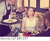 Купить «Waiter male bringing food for male and female», фото № 27347377, снято 11 декабря 2017 г. (c) Яков Филимонов / Фотобанк Лори