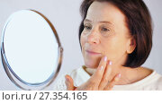 Купить «Woman moisturizes the face with cream», видеоролик № 27354165, снято 5 января 2018 г. (c) Илья Шаматура / Фотобанк Лори