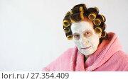 Купить «Wicked wife with a cosmetic mask and curlers», видеоролик № 27354409, снято 5 января 2018 г. (c) Илья Шаматура / Фотобанк Лори