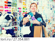 Купить «Female client is standing with purchases», фото № 27354881, снято 10 мая 2017 г. (c) Яков Филимонов / Фотобанк Лори