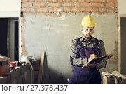 Купить «Worker is writing report about work for client at the object.», фото № 27378437, снято 3 июня 2017 г. (c) Яков Филимонов / Фотобанк Лори