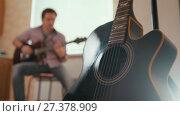 Купить «Young attractive man musician composes music on the guitar and plays, other musical instrument in the foreground, blurred concept», видеоролик № 27378909, снято 16 июля 2018 г. (c) Константин Шишкин / Фотобанк Лори