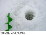 Купить «A hand auger drills and a hole in the ice closeup, winter fishing detail», фото № 27378933, снято 4 января 2018 г. (c) Сергей Дорошенко / Фотобанк Лори