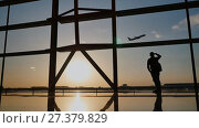 Купить «Silhouette of a tourist guy watching the take-off of the plane standing at the airport window at sunset in the evening. Travel concept, people in the airport.», видеоролик № 27379829, снято 8 января 2018 г. (c) Mikhail Davidovich / Фотобанк Лори
