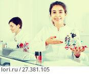 Купить «Female manicurist showing lacquer color schemes», фото № 27381105, снято 2 февраля 2017 г. (c) Яков Филимонов / Фотобанк Лори