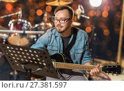 Купить «musician playing guitar at studio over lights», фото № 27381597, снято 18 августа 2016 г. (c) Syda Productions / Фотобанк Лори