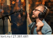 Купить «man with headphones singing at recording studio», фото № 27381681, снято 18 августа 2016 г. (c) Syda Productions / Фотобанк Лори