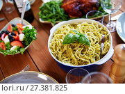 Купить «pasta with basil in bowl and other food on table», фото № 27381825, снято 5 октября 2017 г. (c) Syda Productions / Фотобанк Лори