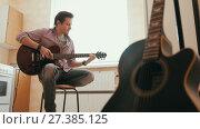 Купить «Young man composes music on the guitar and plays in the kitchen, other musical instrument in the foreground,», видеоролик № 27385125, снято 16 июля 2018 г. (c) Константин Шишкин / Фотобанк Лори
