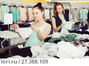 Купить «Positive women friends choosing trousers in shop», фото № 27388109, снято 19 июня 2017 г. (c) Яков Филимонов / Фотобанк Лори