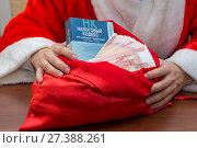 Купить «Волгоград. Россия  - 6 января 2018. Офисный работник в костюме Деда Мороза вытаскивает из мешка с подарками налоговый кодекс и деньги», фото № 27388261, снято 6 января 2018 г. (c) Гетманец Инна / Фотобанк Лори