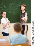 Купить «Schoolchildren with teacher in classroom. Pupil solving task standing at blackboard.», фото № 27388325, снято 16 октября 2019 г. (c) Оксана Кузьмина / Фотобанк Лори