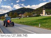 Купить «Трактор едет по шоссе рядом с церковью св. Иоанна. Деревня Обермиллштатт, Каринтия, Австрия», фото № 27388745, снято 8 октября 2017 г. (c) Bala-Kate / Фотобанк Лори