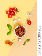Купить «Sun dried tomatoes, champignon mushrooms, fresh tomatoes and basil leaves are ingredients on a yellow-orange pastel background.», фото № 27390205, снято 14 января 2018 г. (c) Olesya Tseytlin / Фотобанк Лори