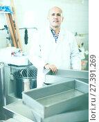 Купить «Worker standing near table in manufacture», фото № 27391269, снято 22 апреля 2017 г. (c) Яков Филимонов / Фотобанк Лори