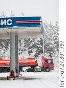 Купить «Оранжевый бензовоз во время слива топлива на автомобильной заправке Сургутнефтегаз в зимнее время года, в снегопад», фото № 27391797, снято 10 января 2018 г. (c) Кекяляйнен Андрей / Фотобанк Лори