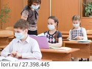 Купить «schoolchildren with protection masks against flu virus at lesson in classroom», фото № 27398445, снято 20 января 2018 г. (c) Оксана Кузьмина / Фотобанк Лори