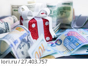 Купить «Red toy gift, dollars and euro on black background», фото № 27403757, снято 17 января 2018 г. (c) Papoyan Irina / Фотобанк Лори