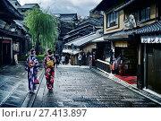 Купить «Two girls in bright Yukata kimonos with their obi tied in a bow walking down Yasaka dori street in Kyoto near Kiyomizu-dera after an autumn rain. Higashiyama, Kyoto, Japan.», фото № 27413897, снято 19 ноября 2017 г. (c) age Fotostock / Фотобанк Лори