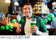 Купить «Man drinking green beer at bar or pub», фото № 27421645, снято 22 апреля 2015 г. (c) easy Fotostock / Фотобанк Лори