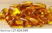 Купить «capsules with fish oil lies on a wooden table», видеоролик № 27424049, снято 26 ноября 2017 г. (c) BestPhotoStudio / Фотобанк Лори