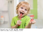 Купить «Happy child boy brushing teeth near mirror in bathroom. He is monitoring lasting of cleaning action with hourglass.», фото № 27425197, снято 20 ноября 2017 г. (c) Оксана Кузьмина / Фотобанк Лори