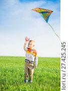 Купить «Young boy playing with his kite in a green field.», фото № 27425245, снято 20 мая 2014 г. (c) Александр Маркин / Фотобанк Лори