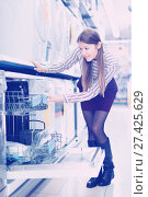 Купить «Modern female housewife buying dishwasher in domestic appliances section», фото № 27425629, снято 12 декабря 2017 г. (c) Яков Филимонов / Фотобанк Лори